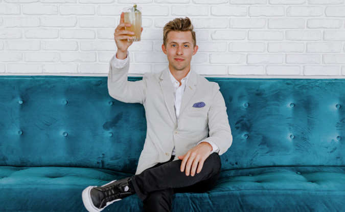 man sitting on couch toasting a drink