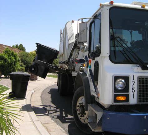 garbage truck picking up trash can