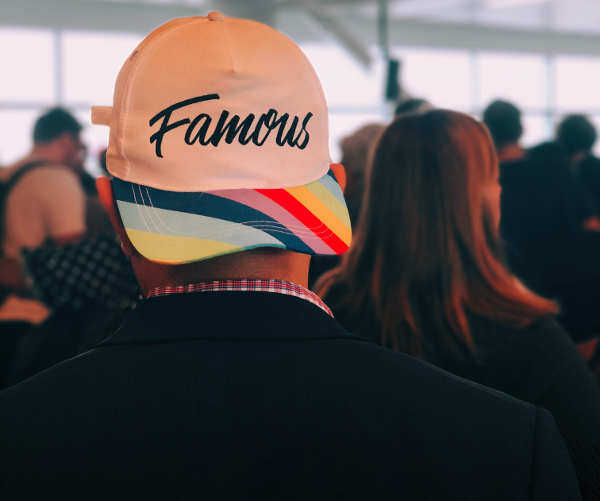 man wearing hat with 'famous' on it