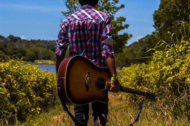 man walking with guitar in nature