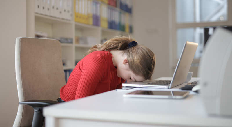 a woman with her head down on her laptop