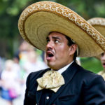 two men singing wearing Spanish clothing and hats
