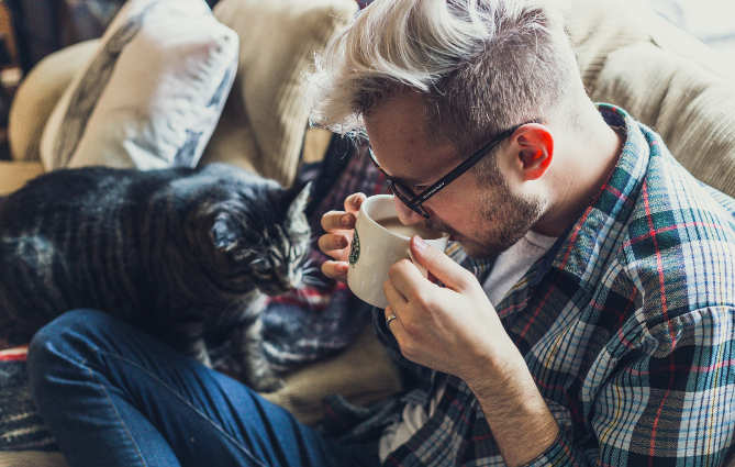 a man drinking coffee with cat on lap